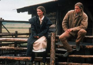 Julia Ormond and Brad Pitt sit on a corral fence