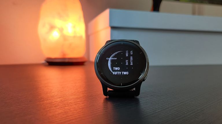 Garmin Venu 2 fitness watch placed on a table in front of a salt lamp