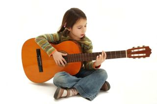 A young girl practices playing her guitar