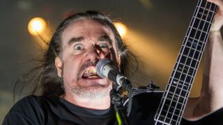 Jeff Walker of Carcass onstage, grimacing into the mic