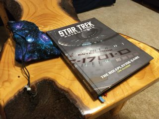 A game book sits on a wooden, tree-trunk-like table next to a galaxy-patterned dice bag.