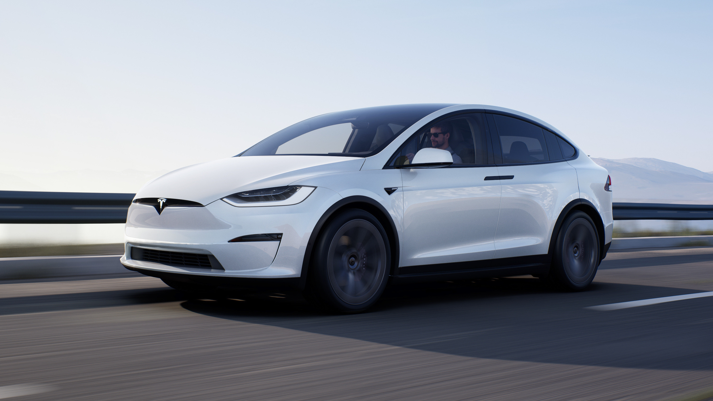 A white Tesla Model X driving on a road