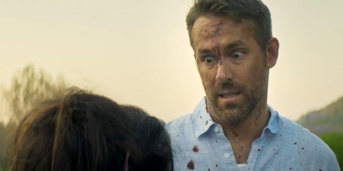 Ryan Reynolds looks horrified in a bloody shirt in The Hitman's Wife's Bodyguard