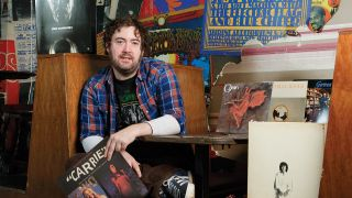 a portrait of Nick Helm with his records