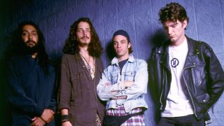 Grunge band Soundgarden standing against a blue wall