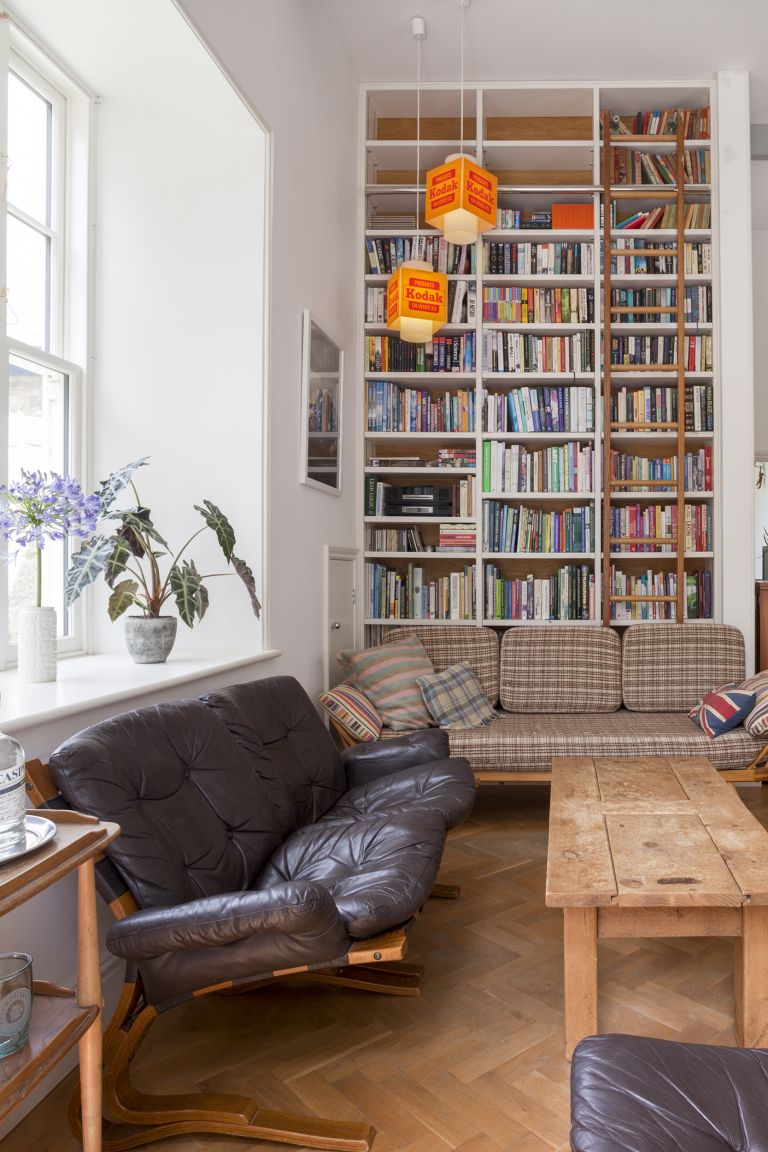 black sofa and checked sofa in living room in front of bookshelf with lots of books