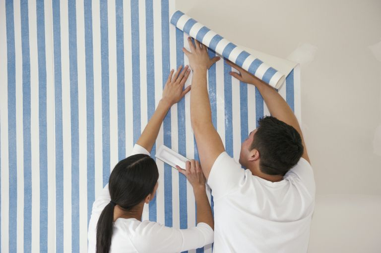 Couple putting up wallpaper, removable wallpaper