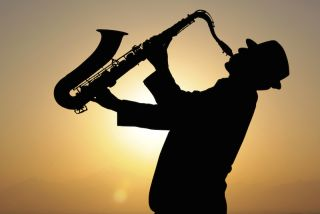 A man plays a saxophone in front of a sunset