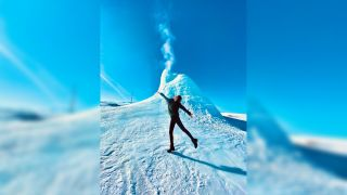 A visitor standing in front of the 'ice volcano' in Kazakhstan.
