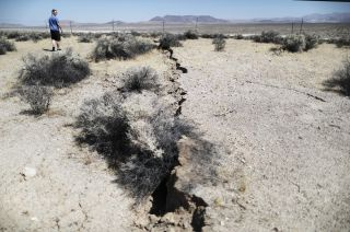 An onlooker views newly ruptured ground after a 7.1-magnitude earthquake struck on July 6, 2019, near Ridgecrest, California.
