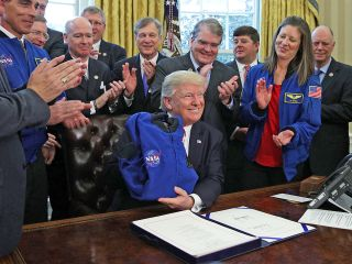 President Trump signed the NASA Transition Authorization Act of 2017 on March 21, surrounded by members of congress. Two NASA astronauts in attendance presented Trump with an astronaut flight jacket.