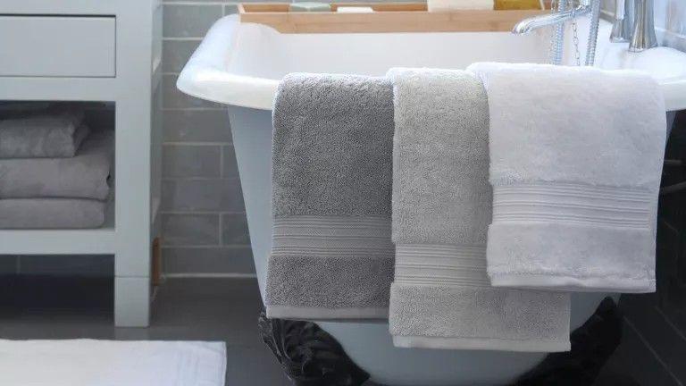 Bath towels hanging off edge of bath
