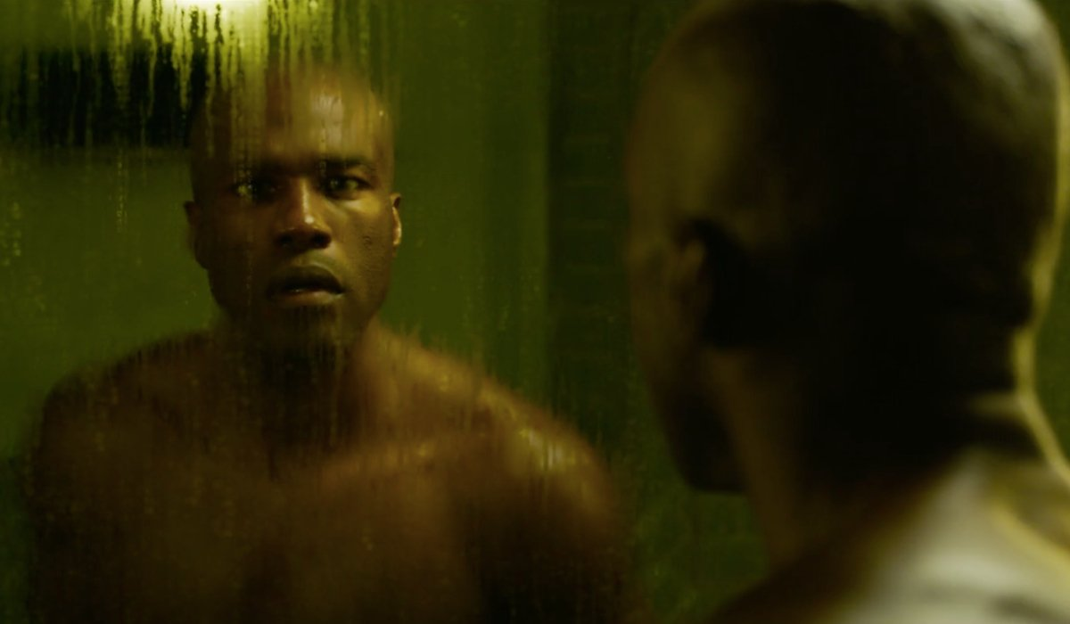 Yahya Abdul-Mateen II looking surprised at his reflection in The Matrix Resurrections.