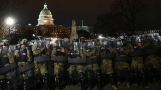 National Guard troops clear a street from protestors outside the Capitol building on Jan. 6, 2021 in Washington, D.C.
