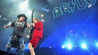 Axl Rose onstage with Angus Young