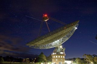 Parkes 64 meter radio telescope with space shuttle Atlantis, International Space Station in the sky behind it.