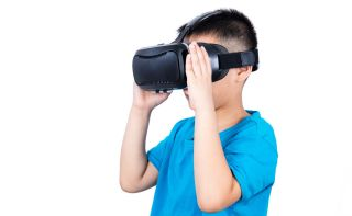 Boy in blue shirt looks through virtual reality goggles