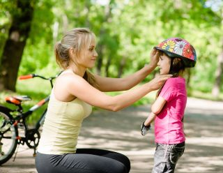 A mom adjusts her daughter's bike helmet.