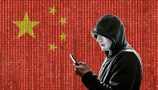 A man wearing a hoodie looks at a smartphone against a backdrop of a Chinese flag overlaid with 'Matrix'-like streams of digits.