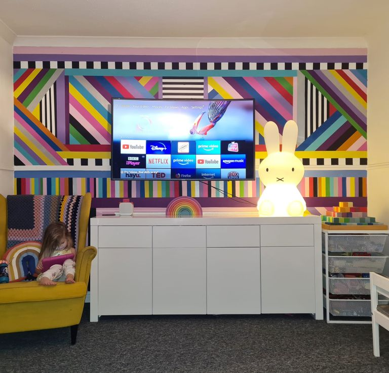 a brightly coloured living room wall painted using samples and masking tape