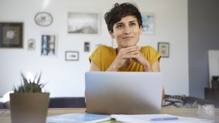 How to create a healthy home office setup: A woman with short dark hair looks happy sat at her home office desk