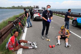 Team JumboVisma rider Netherlands Jos Van Emden R and Team Cofidis rider Eritreas Natnael Berhane L sit on the ground after a massive pack crash during the 15th stage of the Giro dItalia 2021 cycling race a 147km race between Grado and Gorizia on May 23 2021 Photo by Luca Bettini AFP Photo by LUCA BETTINIAFP via Getty Images