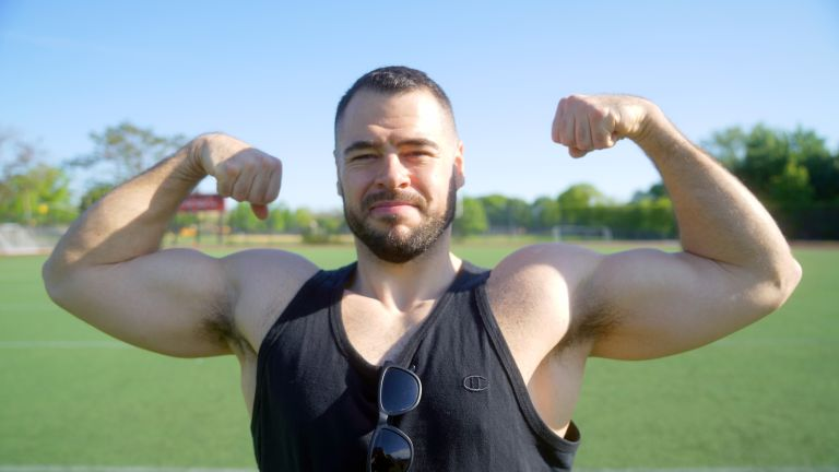 Alex Solomin, fitness coach, flexing for the camera