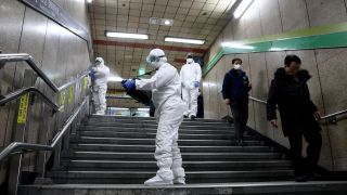 Workers wearing protective gear spray anti-septic solution at a subway station in Seoul, South Korea, on Feb. 21, 2020, as a measure to contain the new coronavirus.