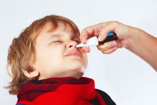 A child receiving a nasal spray