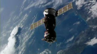 A Russian Soyuz MS-02 spacecraft carrying NASA astronaut Shane Kimbrough and Russian cosmonauts Sergey Ryzhikov and Andrey Borisenko nears the International Space Station ahead of docking in this still image from a video camera on the space station captur