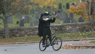 Man rides bicycle while headless and playing guitar