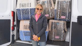 Yulin Dog Meat Festival rescue: Jill Stewart, founder of China Rescue Dogs, standing in front of dogs in transport cages getting ready to be flown to the US