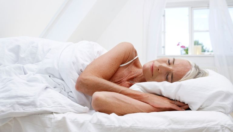 Mature woman sleeping in her bed - stock photo