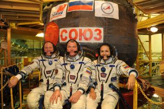 "NASA astronaut Barry ""Butch"" Wilmore (left) and Russian cosmonauts Alexander Samokutyaev (center) and Elena Serova pose with their Soyuz TMA-14M spacecraft ahead of a September 2014 launch to the International Space Station."