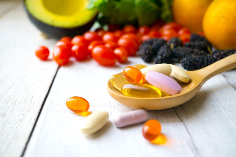 Best multivitamin: tablets on side sitting on wooden spoon with fruit surrounding