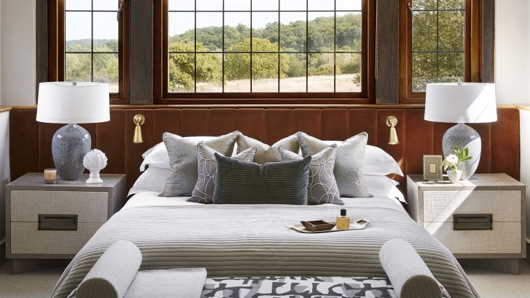 Bedroom furniture ideas with orange-brown velvet headboard, white sheets and grey bench