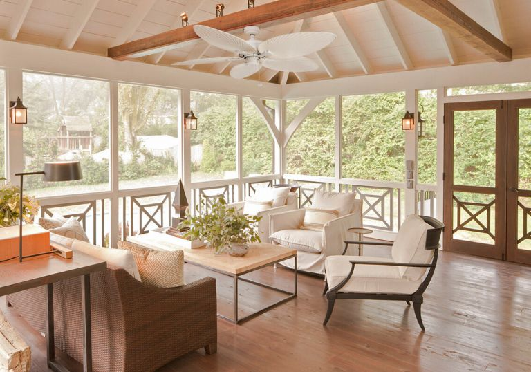 sunroom/porch with wooden flooring neutral sofas and chairs