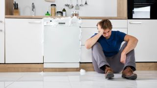 How to unclog a dishwasher: a man sitting in front of a blocked dishwasher