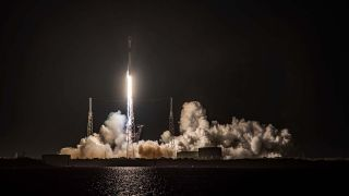 A SpaceX Falcon 9 Rocket Lifting Off From A Launchpad At Night