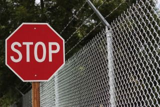 A stop sign and barbed wire fence.