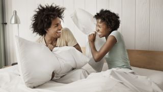 Best pillows for sleeping: A couple engage in a fun pillow fight