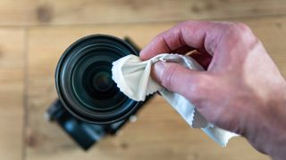 A hand using a cloth to clean a camera lens