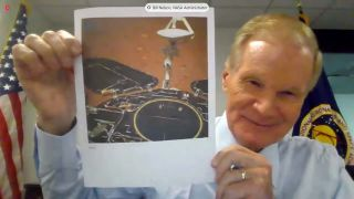 NASA Administrator Bill Nelson holds up a photo of China's Zhurong Mars rover during a House hearing on May 19, 2021.