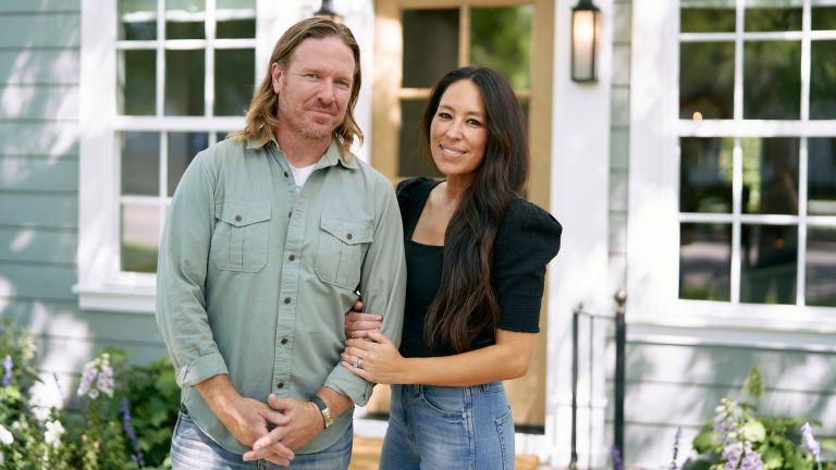 Chip and Joanna Gaines posing in front of Fixer Upper project