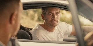 Brian O'Conner (Paul Walker) looks over at Dominic Toretto (Vin Diesel) in Furious 7 (2015)