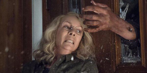 Jamie Lee Curtis Laurie Strode blocking a door Michael Myers reaching in 2018 Halloween