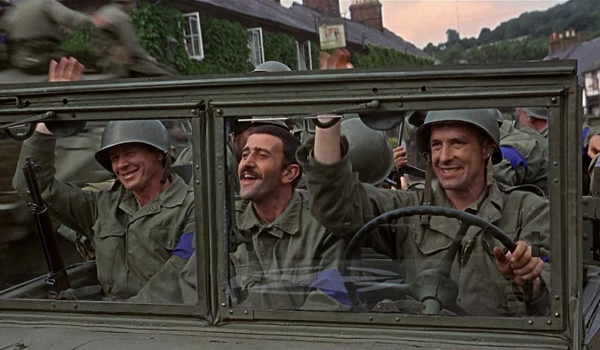 The Dirty Dozen driving through a village and waving at the locals
