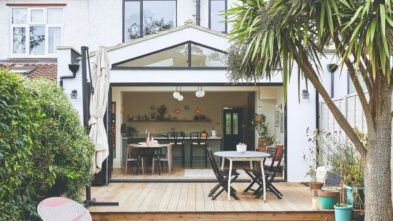 Lea-Wilson house: Rear of house with white extension, wood decking with steps down to grass, outdoor table and chairs
