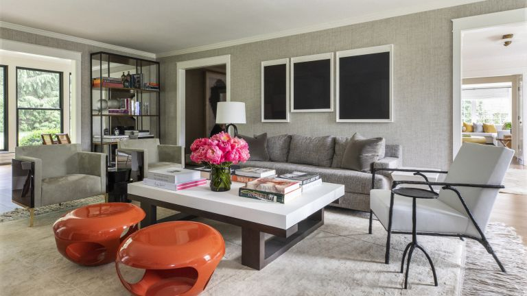 A grey living room with textured wallpaper, grey sofa and orange modern stools