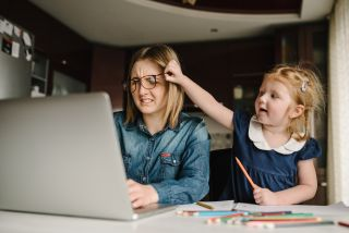 woman working from home while kid messes with her glasses